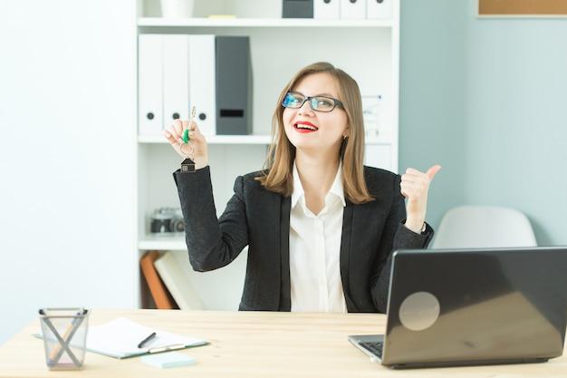 Imobiliário, nova casa e conceito de pessoas de negócios - feliz corretora de imóveis entregando as chaves e mostrando o polegar