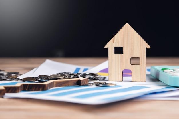 Imóveis, modelos de casas e seta com calculadora no gráfico