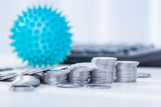 Impacto do coronavírus na economia. moedas, calculadora em cima da mesa. medicina e dinheiro conceito, despesas para covid-19.