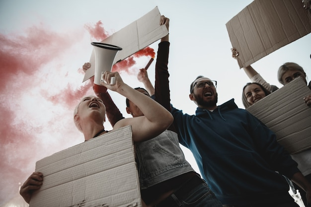 Imparável. grupo de ativistas dando slogans em um comício. homens e mulheres caucasianos marchando juntos em um protesto na cidade. pareça zangado, esperançoso, confiante. banners em branco para seu projeto ou anúncio.