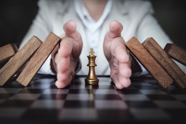 Impedindo o risco de jogar xadrez em um quadro de negócios, conceito de seguro comercial.