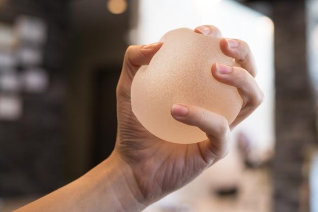 Implante mamário de silicone nas mãos