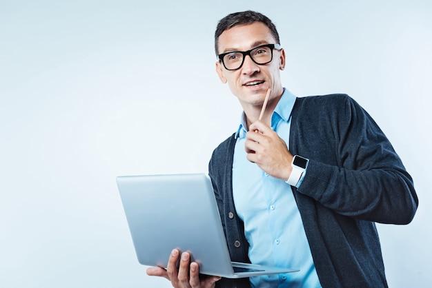 Implementando ideias. cara inteligente com um laptop focando em suas idéias, enquanto está de pé sobre o fundo com um laptop nas mãos e pensando.