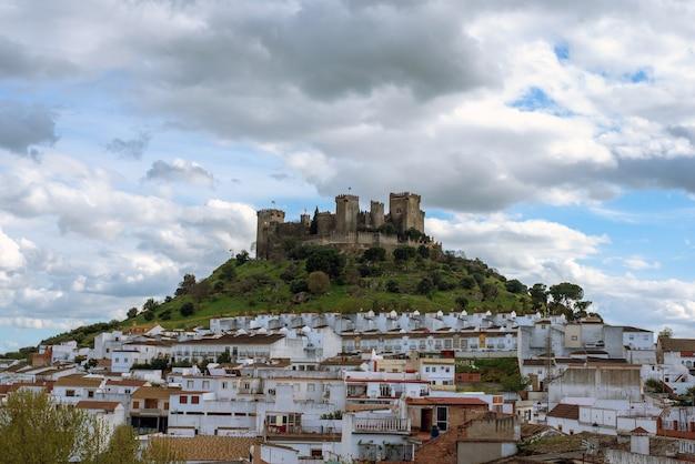 Imponente castelo de almodovar del rio, no topo da colina e a seus pés construções habitacionais