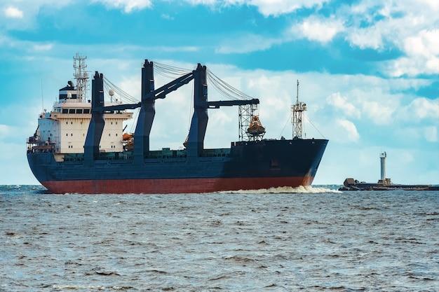 Importação de mercadorias. grande navio de carga azul movendo-se para o porto de riga