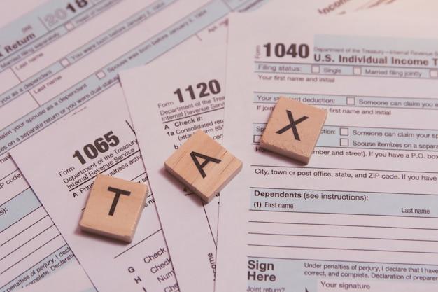 Imposto com blocos de madeira alfabeto, caneta em fundo de formulário de imposto dos eua