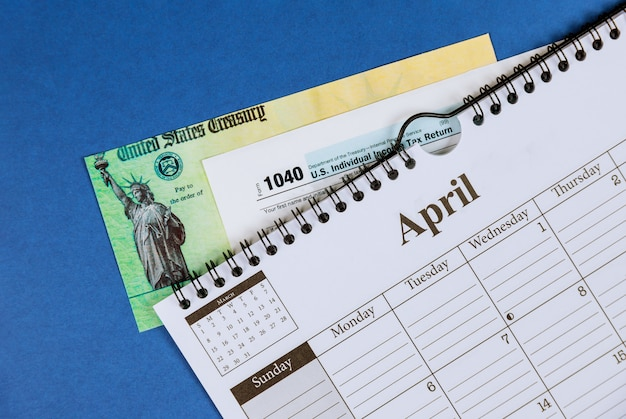 Imposto de renda com formulário 1040 e calendário espiral em abril
