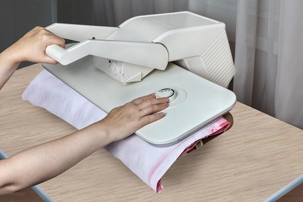 Imprensa a vapor de mesa para roupas, close-up de mãos femininas passando roupas.