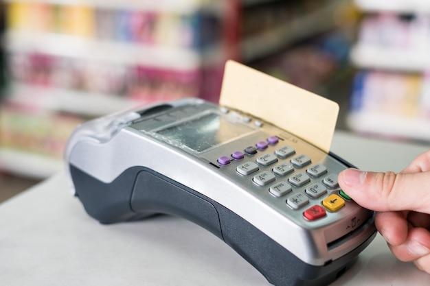 Imprensa de mão com swiping cartão de crédito no terminal de pagamento na loja