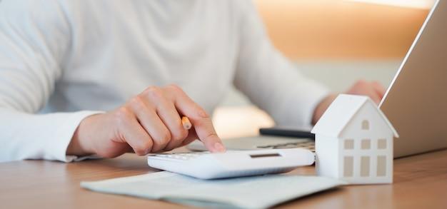 Imprensa de mão de homem na calculadora para verificar e resumir as despesas da hipoteca de empréstimo à habitação para refinanciar o plano