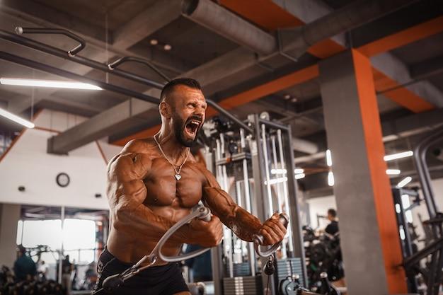 Imprensa no peito. homem sexy musculoso bonito no ginásio fazendo exercícios. atleta bronzeada. treinos no peito.