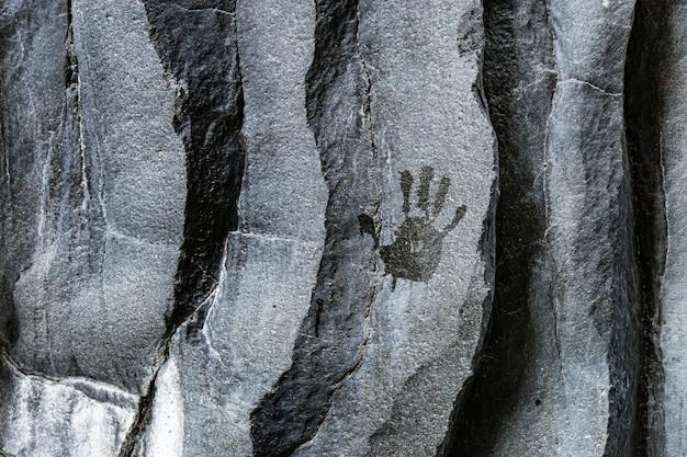 Impressão da mão do homem em pedras vulcânicas