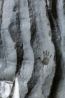 Impressão da mão molhada do homem na parede de pedra vulcânica