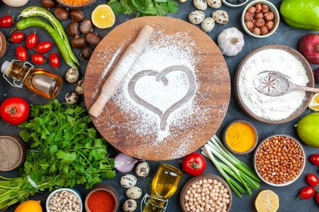 Impressão de coração de rolo de massa em farinha em pó em uma placa de massa redonda Foto gratuita