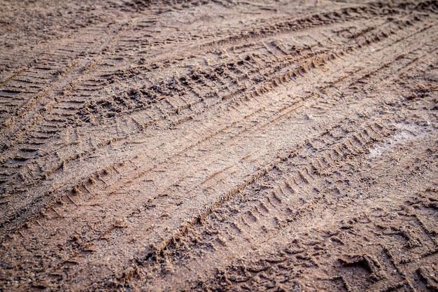 Impressão de faixa de pneu de motocicleta e carro na areia ou lama com foco seletivo