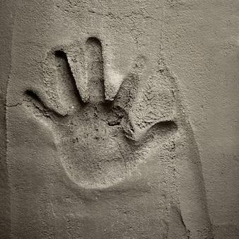 Impressão de mão na parede de argamassa de cimento