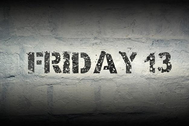 Impressão do estêncil de sexta-feira 13 na parede de tijolos brancos do grunge
