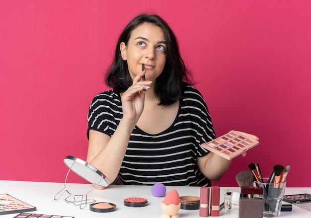 Impressionada ao olhar para uma jovem bonita sentada à mesa com ferramentas de maquiagem segurando uma paleta de sombra com pincel de maquiagem isolado na parede rosa