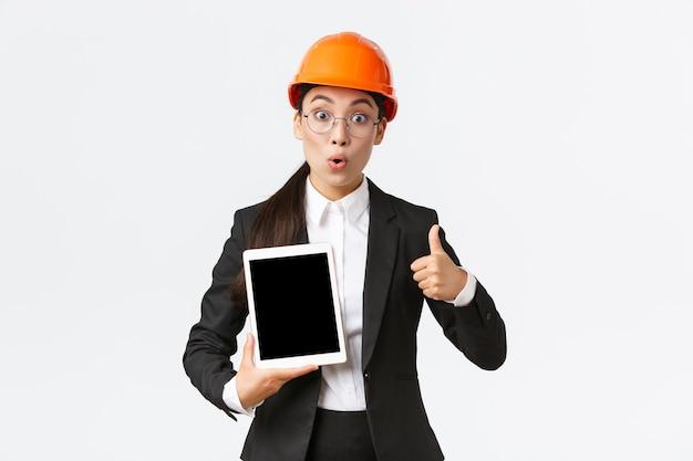 Impressionada e entusiasmada, engenheira asiática, técnica industrial de terno e capacete de segurança mostrando o polegar para cima e a tela do tablet digital com expressão de espanto, reage ao diagrama de lucro