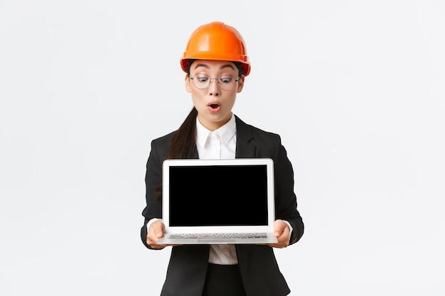Impressionada, engenheira, arquiteta ou gerente de construção asiática na empresa, mostrando a tela do laptop com expressão de espanto, olhando para o diagrama de lucro durante a reunião, use capacete de segurança na fábrica