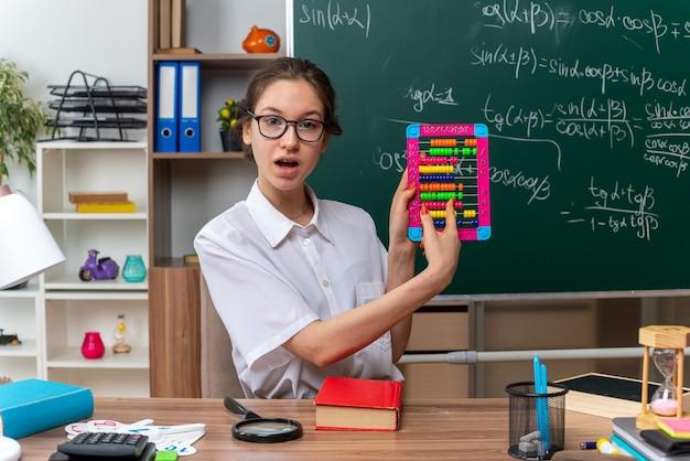 Impressionada jovem professora de matemática usando óculos, sentada na mesa com o material escolar, mostrando o dedo indicador do ábaco olhando para a frente na sala de aula