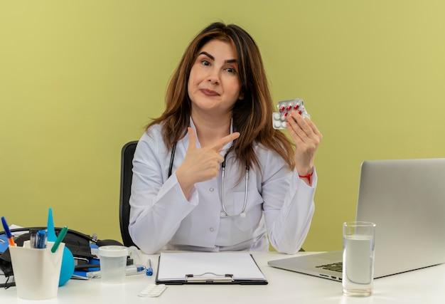 Impressionada médica de meia-idade usando manto médico e estetoscópio sentada à mesa com ferramentas médicas e um laptop segurando e apontando para medicamentos isolados