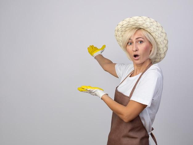 Impressionada mulher loira de meia-idade, jardineira, de uniforme, usando chapéu e luvas de jardinagem, em vista de perfil, olhando para frente apontando com as mãos para trás