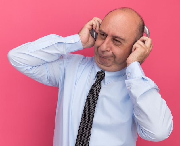 Impressionado ao olhar para o lado de um homem de meia-idade vestindo uma camiseta branca com gravata e fones de ouvido isolados na parede rosa