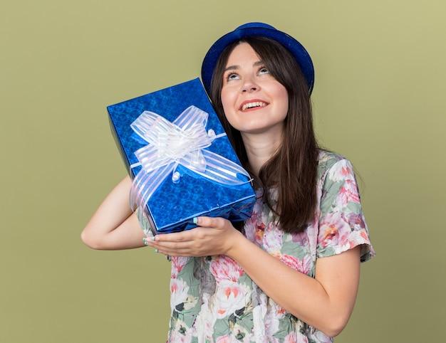 Impressionado ao olhar para uma jovem linda com um chapéu de festa segurando uma caixa de presente ao redor do rosto, isolada na parede verde oliva