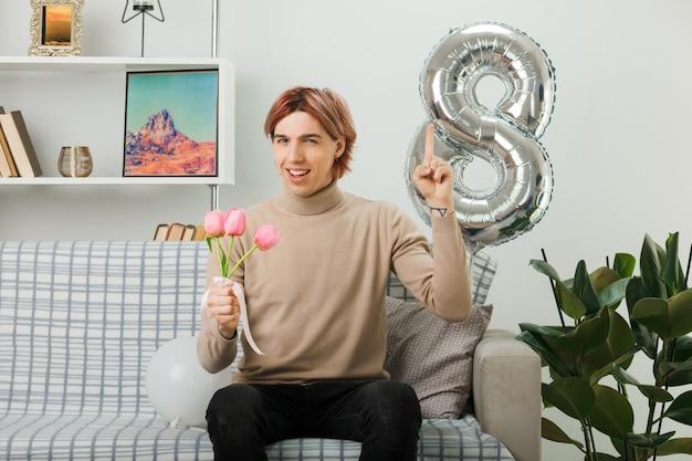 Impressionado, aponta para um cara bonito no feliz dia da mulher segurando flores sentado no sofá da sala de estar