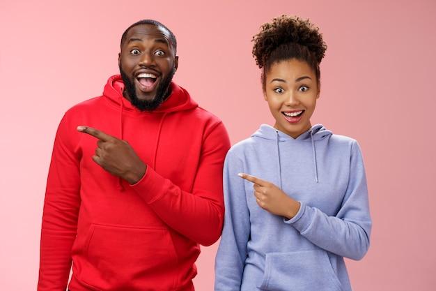 Impressionado dois melhores amigos afro-americanos homem mulher 25 anos caem queixo divertido visitar incrível parque interessante apontando o dedo indicador esquerdo arregalar os olhos emocionados se divertindo juntos, em pé fundo rosa
