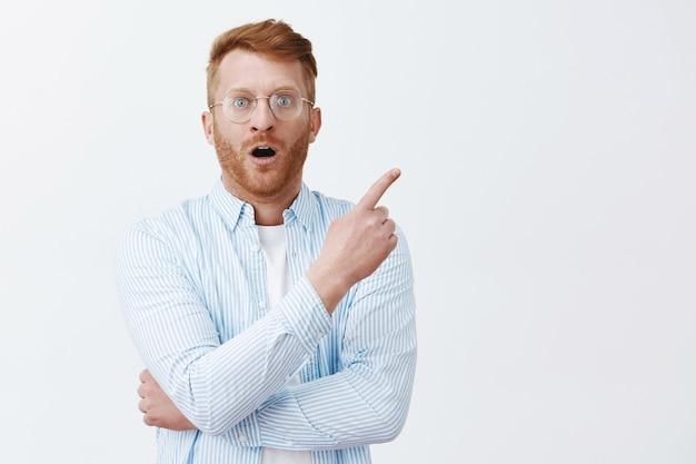 Impressionado e surpreso, homem ruivo europeu bonito com cerdas nos óculos e camisa, apontando para o canto superior direito com o queixo caído e olhar surpreso, parado fascinado sobre uma parede cinza