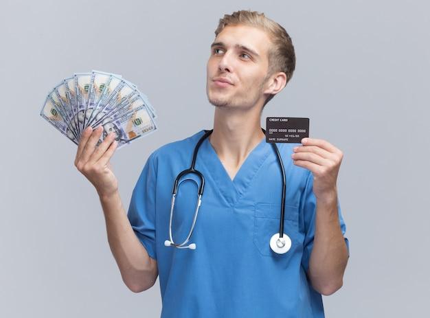 Impressionado olhando para o lado jovem médico vestindo uniforme de médico com estetoscópio segurando dinheiro e cartão de crédito isolado na parede branca