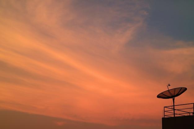Impressionante cor vibrante do sol afterglow com a silhueta da antena parabólica