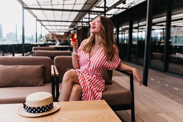 Impressionante menina loira caucasiana rindo enquanto bebe vinho no dia de verão. foto de adorável modelo feminino em vestido listrado, posando em um café aconchegante.