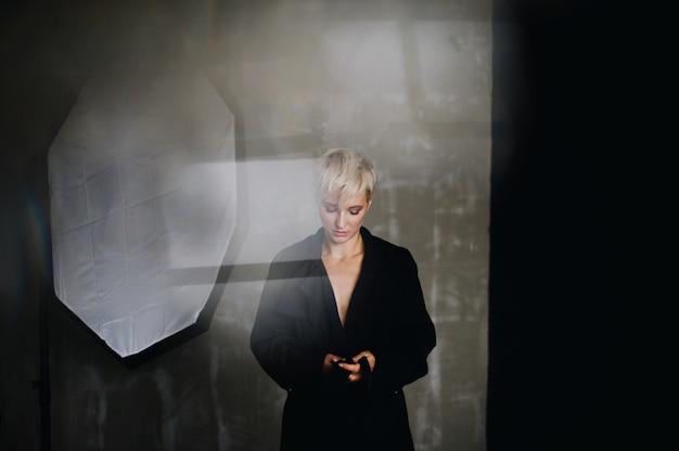 Impressionante modelo com cabelo branco curto coloca no casaco preto antes de um soft-box