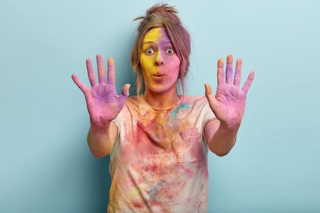 Impressionante mulher europeia surpreendeu a expressão facial, mostra as duas palmas coloridas, o rosto manchado de pó, olha fixamente em choque e a camiseta suja brinca com cores no festival holi. conceito de reação