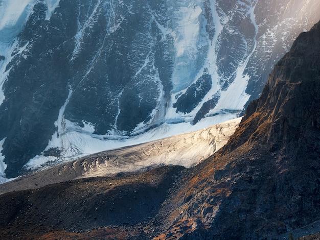 Impressionante paisagem montanhosa com uma enorme montanha nevada e uma geleira iluminada pelo sol entre altas rochas. impressionante cenário alpino com uma grande geleira no topo da montanha.