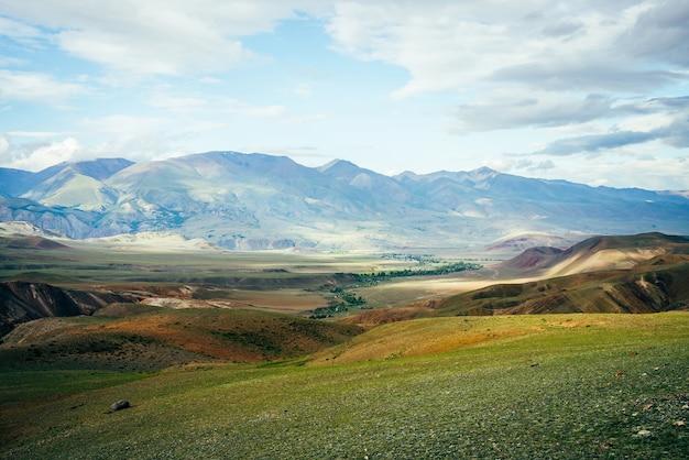 Impressionante paisagem montanhosa vívida com pequeno rio no vale.