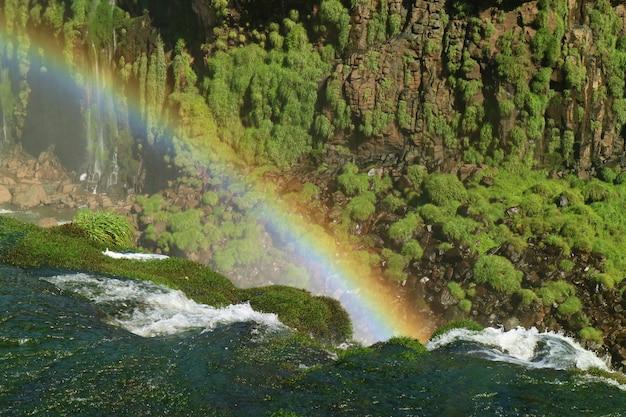 Impressionante vista de um enorme arco-íris sobre as cataratas do iguaçu, foz do iguaçu, brasil, américa do sul