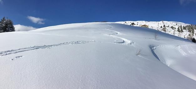 Impressões de esqui na montanha coberta de neve fresca sob o céu azul