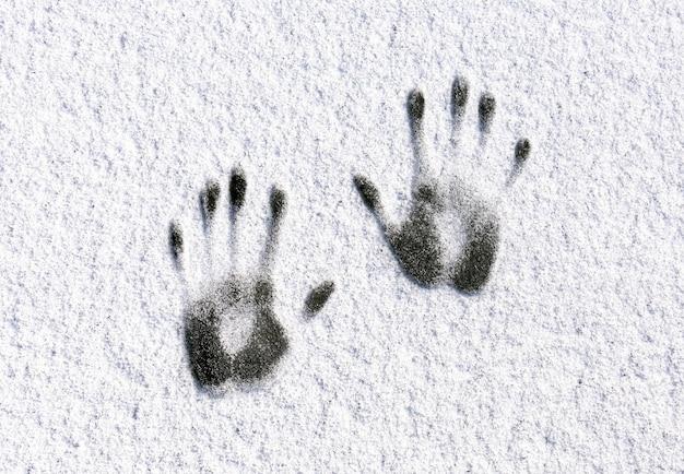Impressões de mãos humanas simétricas na neve branca. conceito de inverno.