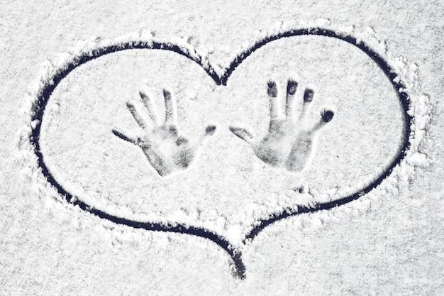 Impressões de mãos na neve circuladas no coração, fundo