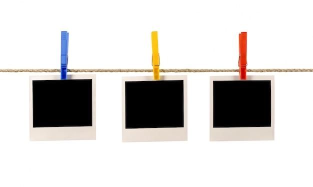 Impressões do polaroid que penduram em uma corda