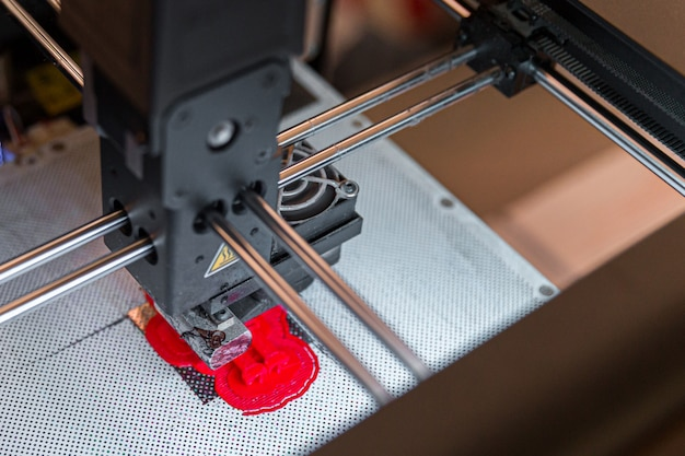 Impressora 3d moderna, imprimindo pequena figura vermelha, closeup vista de cima