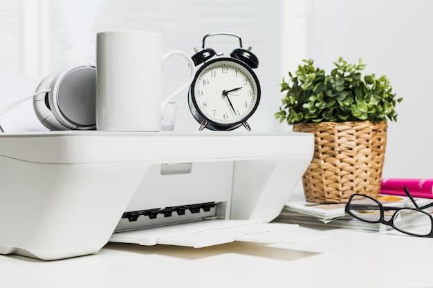 Impressora doméstica branca e fones de ouvido brancos na mesa de escritório