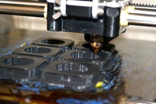 Impressora imprimindo objetos cinza em close-up da superfície reflexiva do espelho