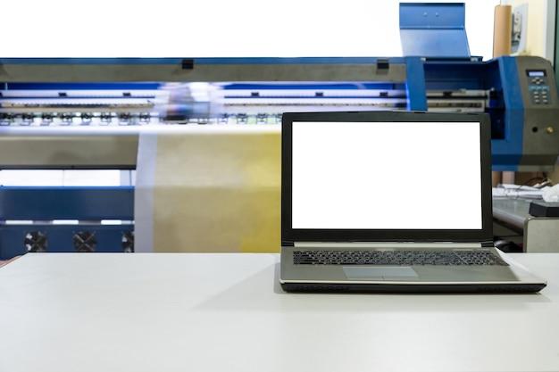 Impressora jato de tinta grande trabalhando em banner de vinil com laptop