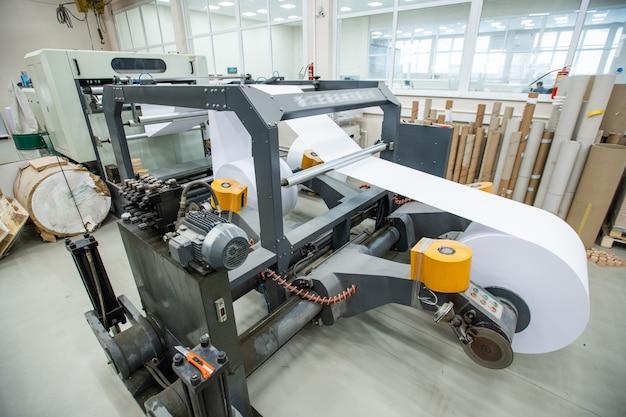 Impressora poderosa com rolo de papel usado para a produção de jornal em uma fábrica moderna