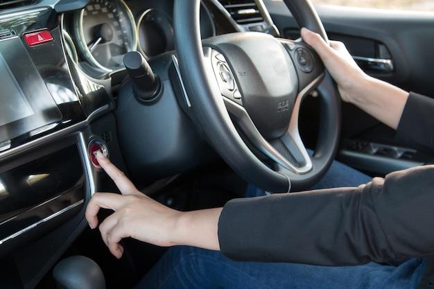 Impulso da mulher de negócio um começo do motor ou botão de parada no carro moderno, fim acima.